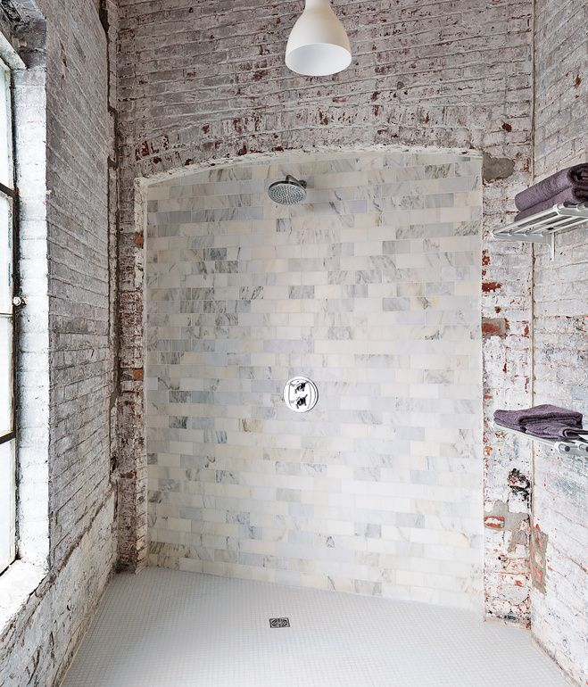 The bathroom evokes the building's industrial bones. The pendant light is from Ikea, and the towel racks are repurposed train car luggage...