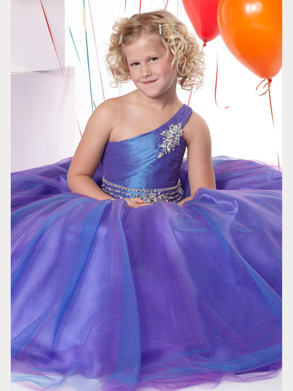 Tiffany Princess Girl Pageant Dress 13281. This ball gown features an asymmetrical neckline accented with cluster of beads, rhinestones and sequins. a pleated bodice with beads and sequin accents and a full tulle skirt. Tailored in Taffeta/Tulle.