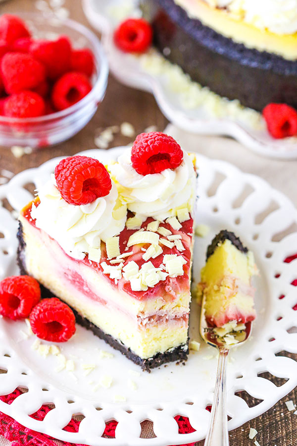 White Chocolate Raspberry Cheesecake #whitechocolateraspberrycheesecake This White Chocolate Raspberry Cheesecake is a creamy white chocolate cheesecake swirled with raspberry filling, all set in a chocolate cookie crust! #cheesecake #raspberry #whitechocolateraspberrycheesecake