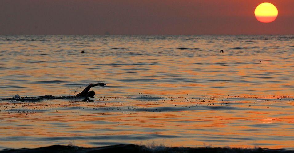 Nadador se exercita durante o pôr do sol na praia de Copabana, no Rio de Janeiro