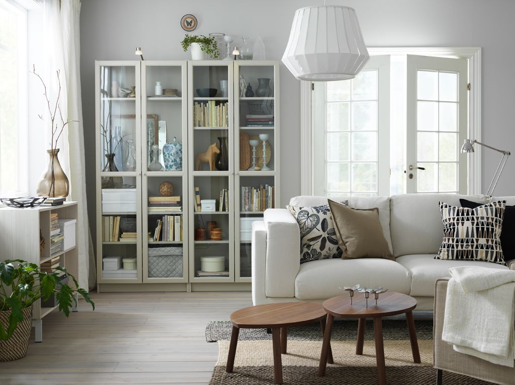 A Small Livingroom Furnished With A Light Beige Two Seat Sofa And Two Beige Glass Door Cabi With Images Bookcase With Glass Doors Ikea Living Room Small Living Room Chairs