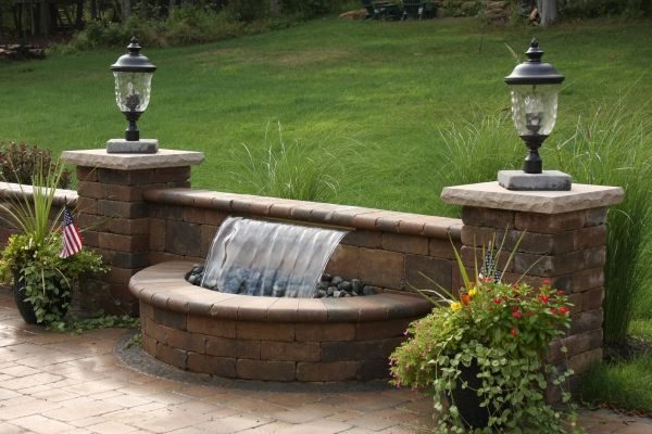 Waterfall by Funyak Landscapes springs out from a garden wall. http://www.housetrends.com/specialist/Funyak-Landscapes