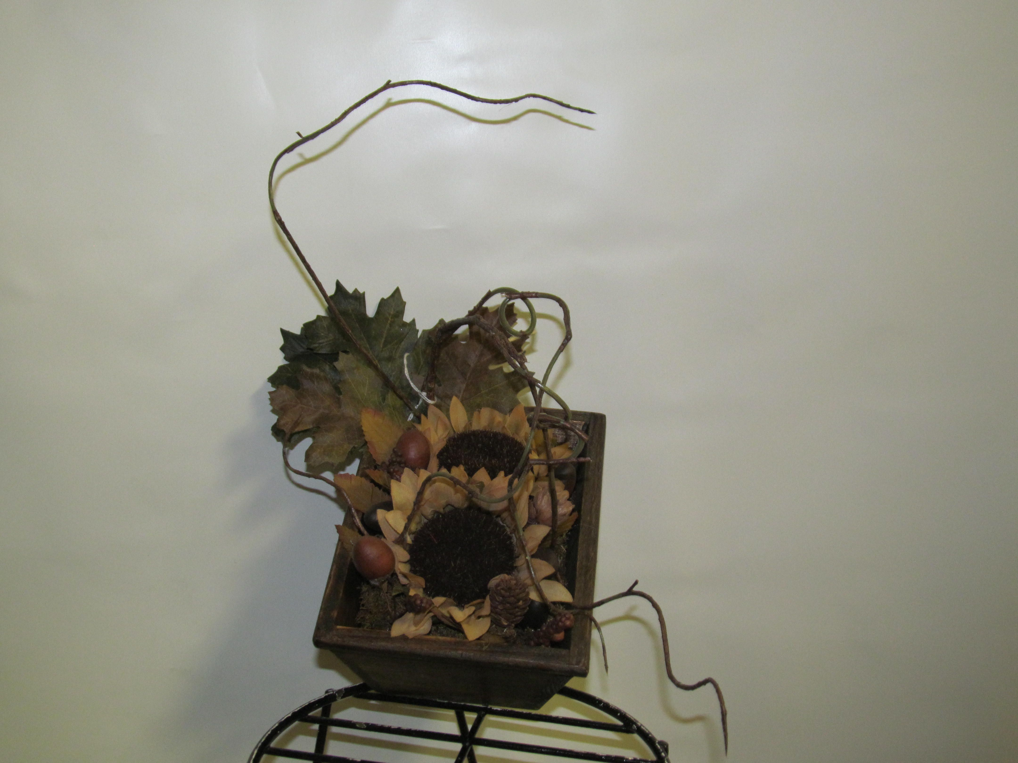 Wooden box with sunflowers and twigs.
