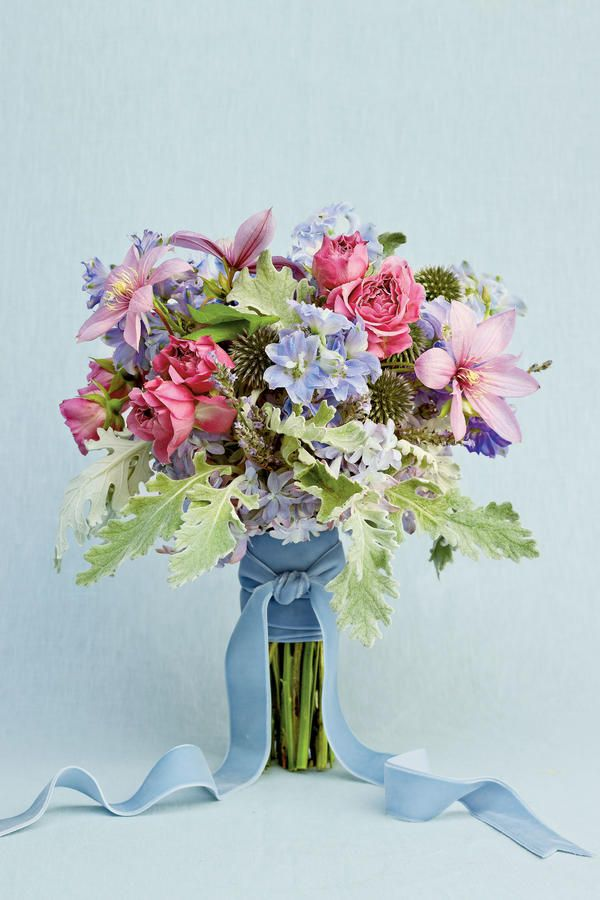Organic Blue and Lavender Blooms - Blue Wedding Flowers - Southernliving. Lavender spray roses, lavender clematis, delphinium, and dusty miller are bundled together with an icy blue velvet ribbon for a bouquet that is perfect for a cheery countryside fête. Globe thistle adds a spiky texture to the soft blooms of this bouquet, giving it a modern edge.