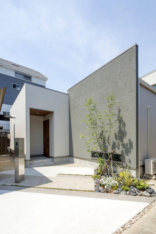 タイル アクセントのグレーの塗り壁 木目調の軒天と玄関扉が効いてい