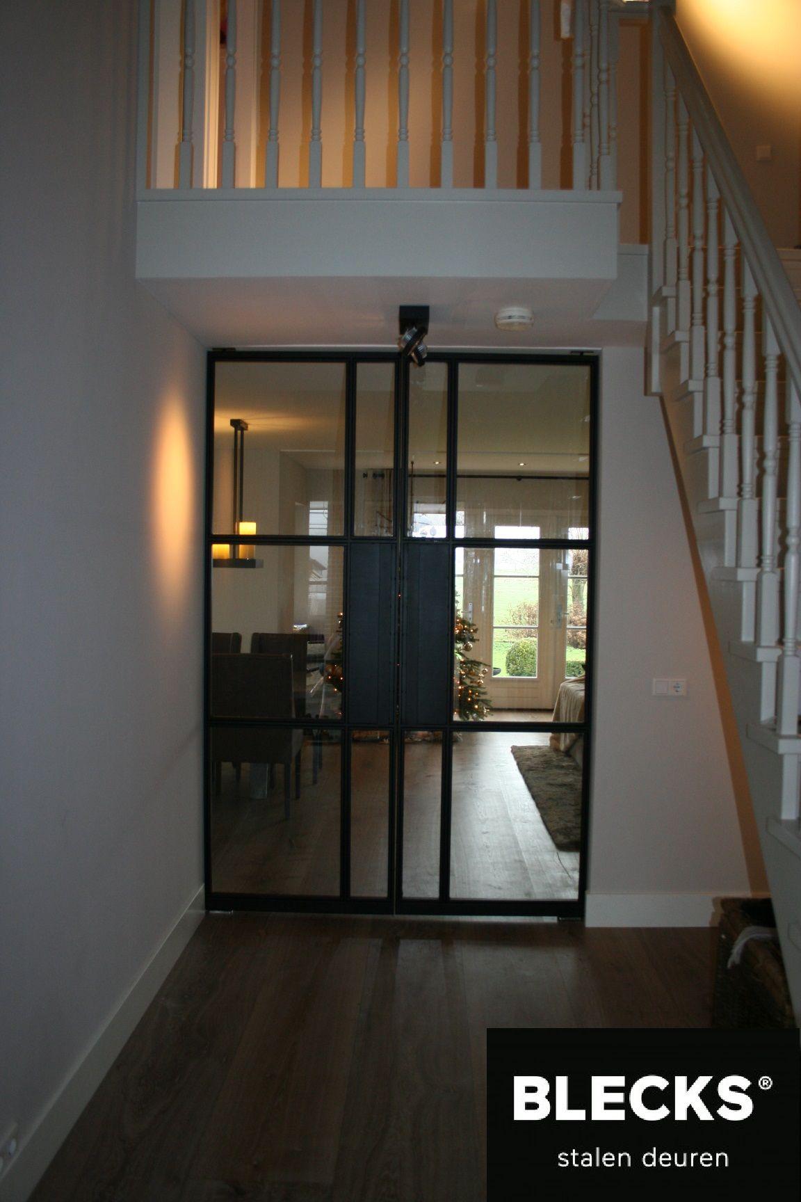 Een prachtige stalen deur onder de trap tussen de hal en de ...