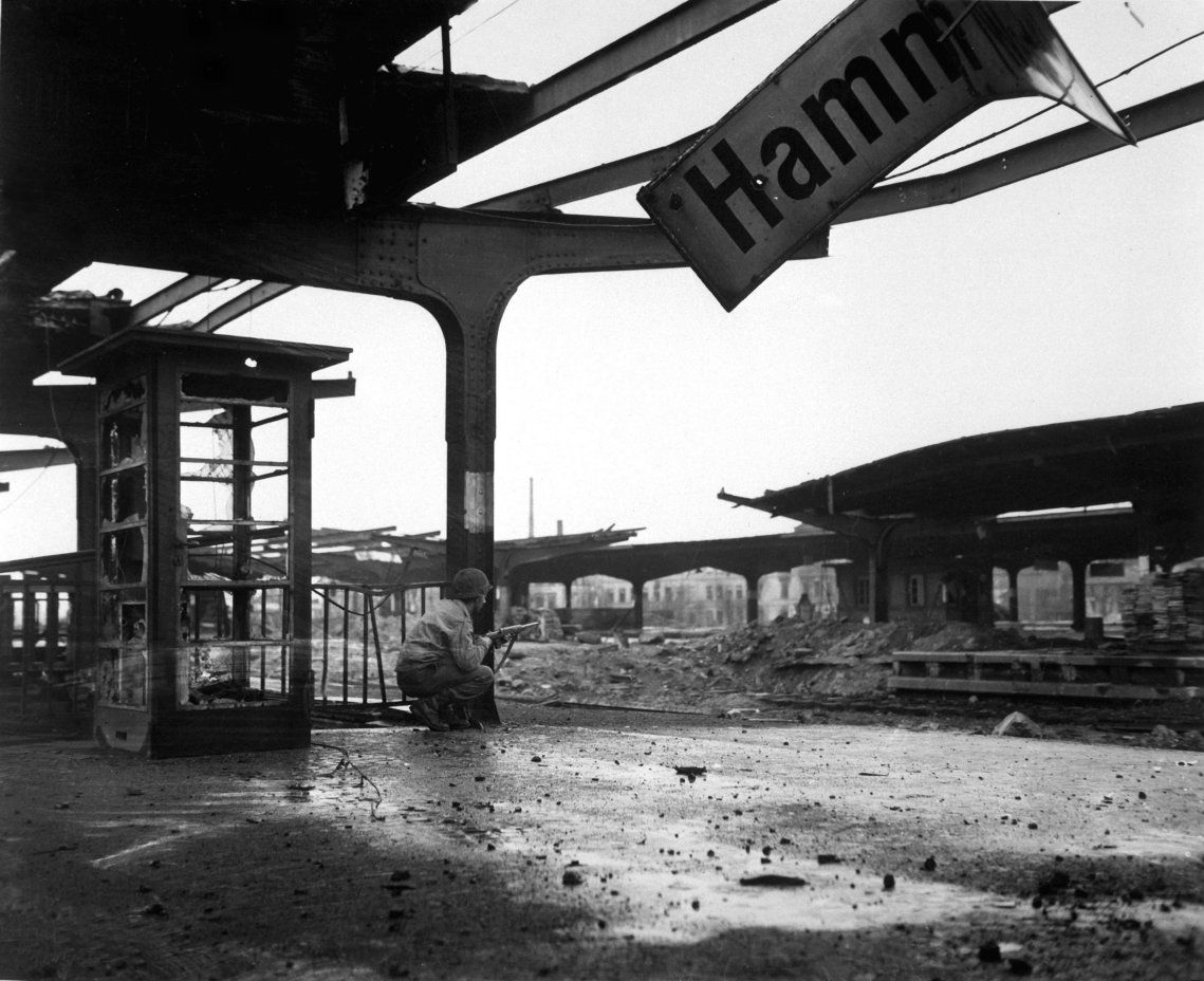 Alert for enemy movement in the newly captured city of Hamm, U.S. Army Pfc. Armand Rindone of Philadelphia, Pennsylvania, crouches with a carbine at the city's railroad station. Hamm, North...