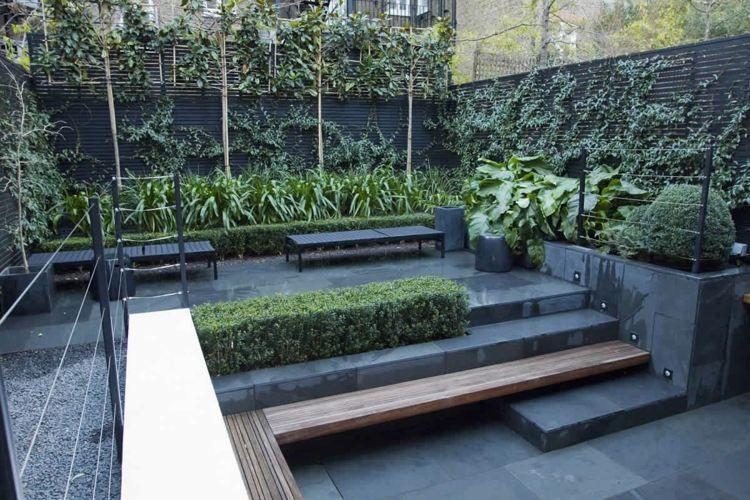 Ein kleiner Garten im modernen Stil aus dunklem Stein und Pflanzen ...
