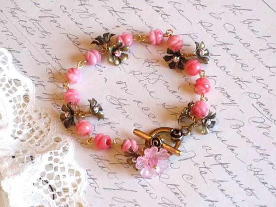Handmade Charm Bracelet. I first linked together 8mm pink carved bamboo coral beads. Then I wire wrapped vintage metal flowers as charms to the bracelet links