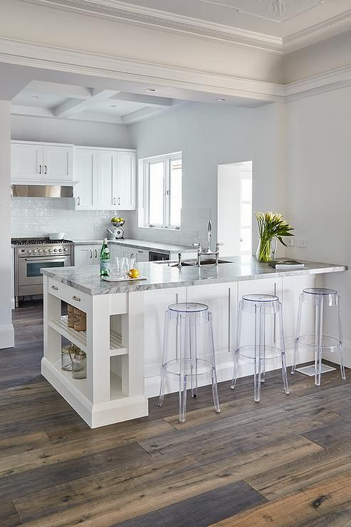 Backless Acrylic Stools Sit In Front Of A White Kitchen Peninsula Accented With Slated Shelves And A S Kitchen Design Small Kitchen Design Decor Kitchen Layout