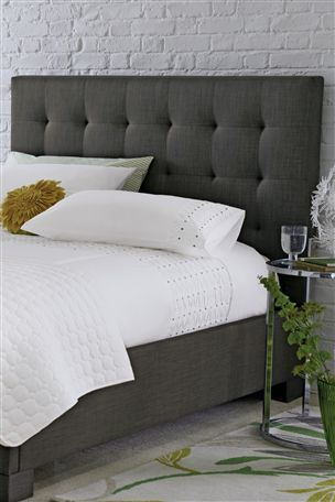 charcoal grey, upholstered headboard with white linens