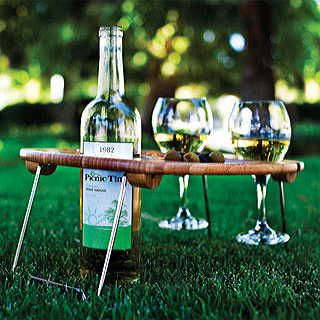 """Create the perfect relaxing picnic atmosphere with this unique, handcrafted wine tray. Made of solid bamboo, with carved-out sections to hold one wine or champagne bottle and two glasses, it's both convenient and elegantly attractive. There's even a spacious central area to place your favorite appetizers between the bottle and glasses. And when the picnic is over, the sturdy chrome-plated legs fold flat against the tray, for easy storage and transport. Dimensions: 13"""" x 4"""" x 17½""""."""