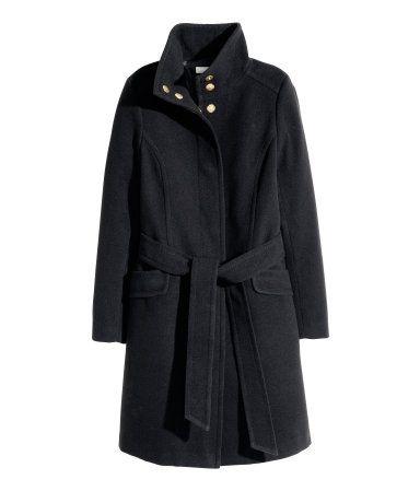 Frakke med let vidde i filtet kvalitet. Frakken har opretstående krave og skjult lukning med trykknapper foran. Bindebælte i taljen og sidelommer med dekorativ klap. Slids bagpå. Med for.
