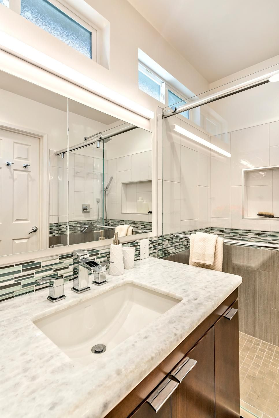Neutral floor tile and vertical gray half wall tile in the shower neutral floor tile and vertical gray half wall tile in the shower join the thin blue and green backsplash tile border and the gray and white counte dailygadgetfo Images
