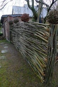 selbst gefertigter Flechtzaun aus Weidenruten mit Kugeln