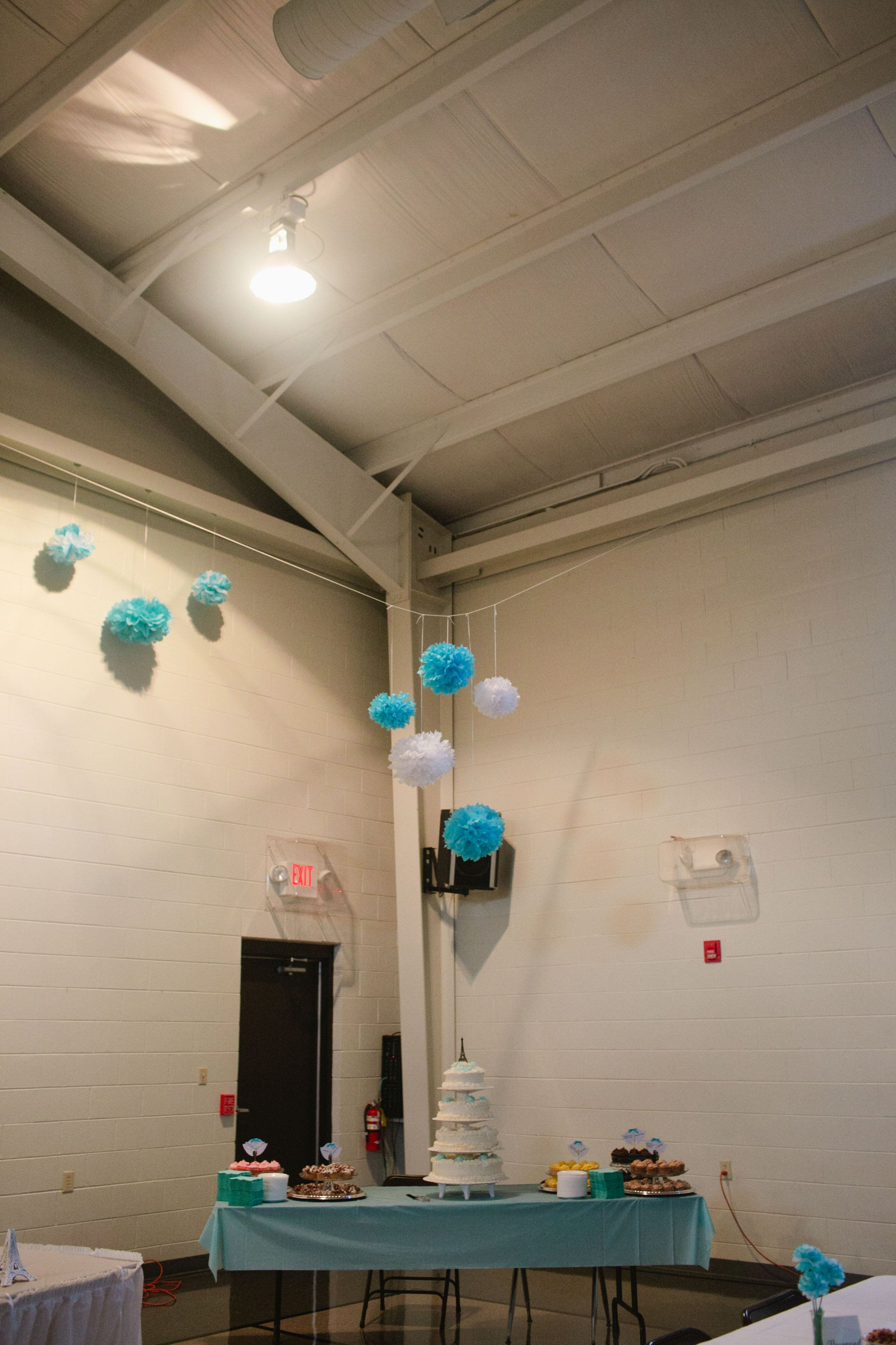 Tissue paper pom-pons above cake table (Maggie & Jeremiah's wedding) #wedding #caketable #tissepaper #pompoms