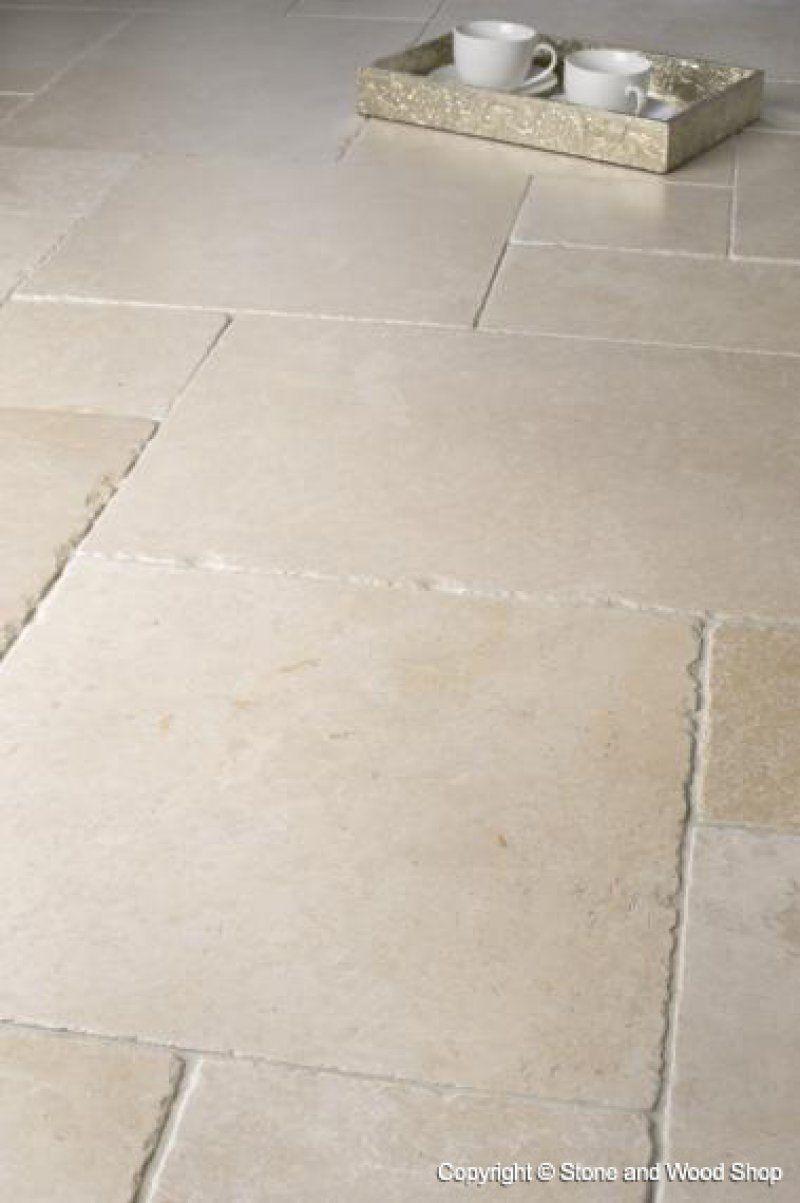 een lichte natuurstenen vloer met onregelmatig gevormde tegels in