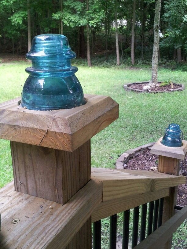 Vintage glass insulators used as post caps! have to put a solar light into it some how