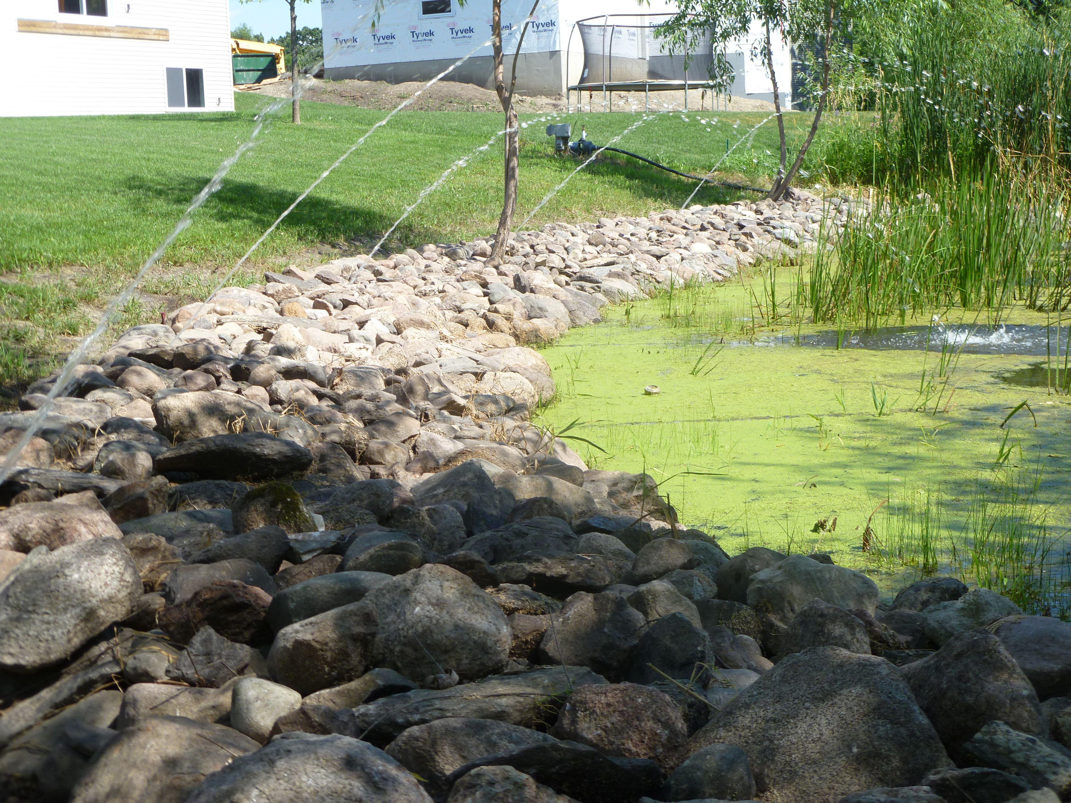 diy fieldstone rock shore on a holding reserve backyard pond to