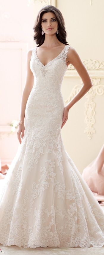 This sleeveless beaded lace fit and flare wedding dress features a beaded V-neckline, a dropped waistline, a scalloped hemline, and a chapel length train.