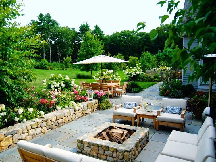 jardín amplio con lugar de fuego y muralla de piedra jardines