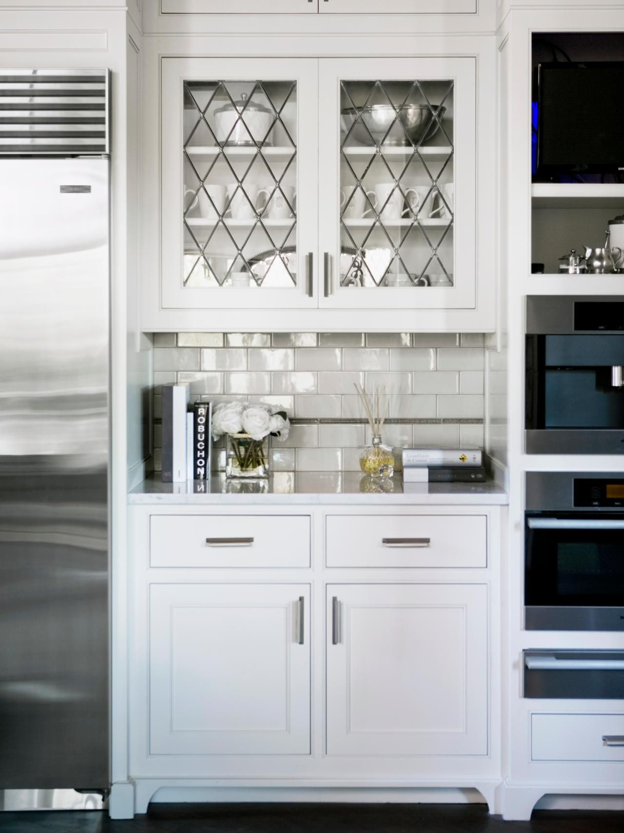 Nice Glass Front Cabinets Hang Above A Subway Tile Backsplash In This White  Kitchen Nook.