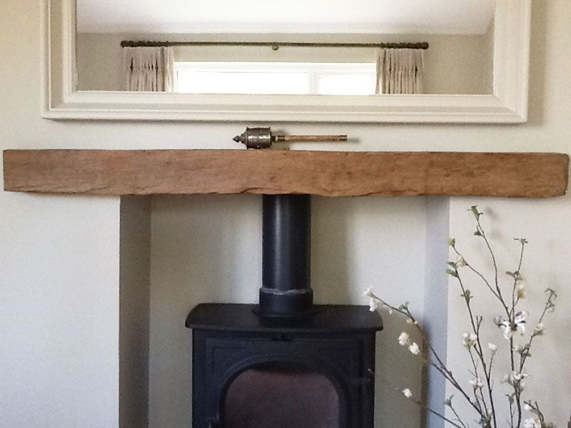 A reclaimed oak beam fireplace lintel housing a wood burning stove ...
