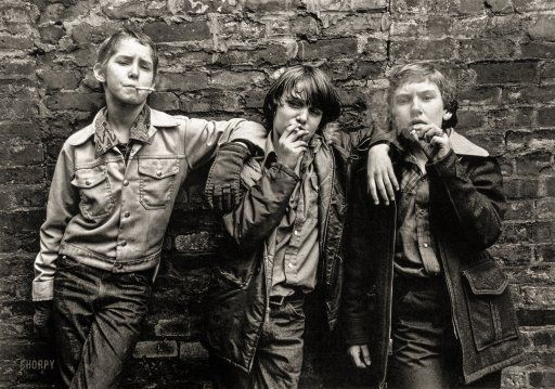 """New York City, 1975. """"Three boys with tough expressions smoking cigarettes."""" Compare with Lewis Hine's photo Skeeter's Branch Newsies, from 65 years earlier. Gelatin silver print by William J. Cunningham."""