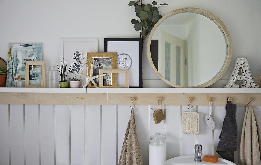 Een spiegel, planten, afbeeldingen en schelpen op een plank in de ...