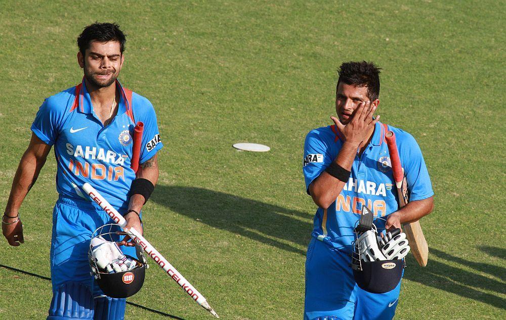 Indian batsman Virati Kohli and Suresh Raina walk off the