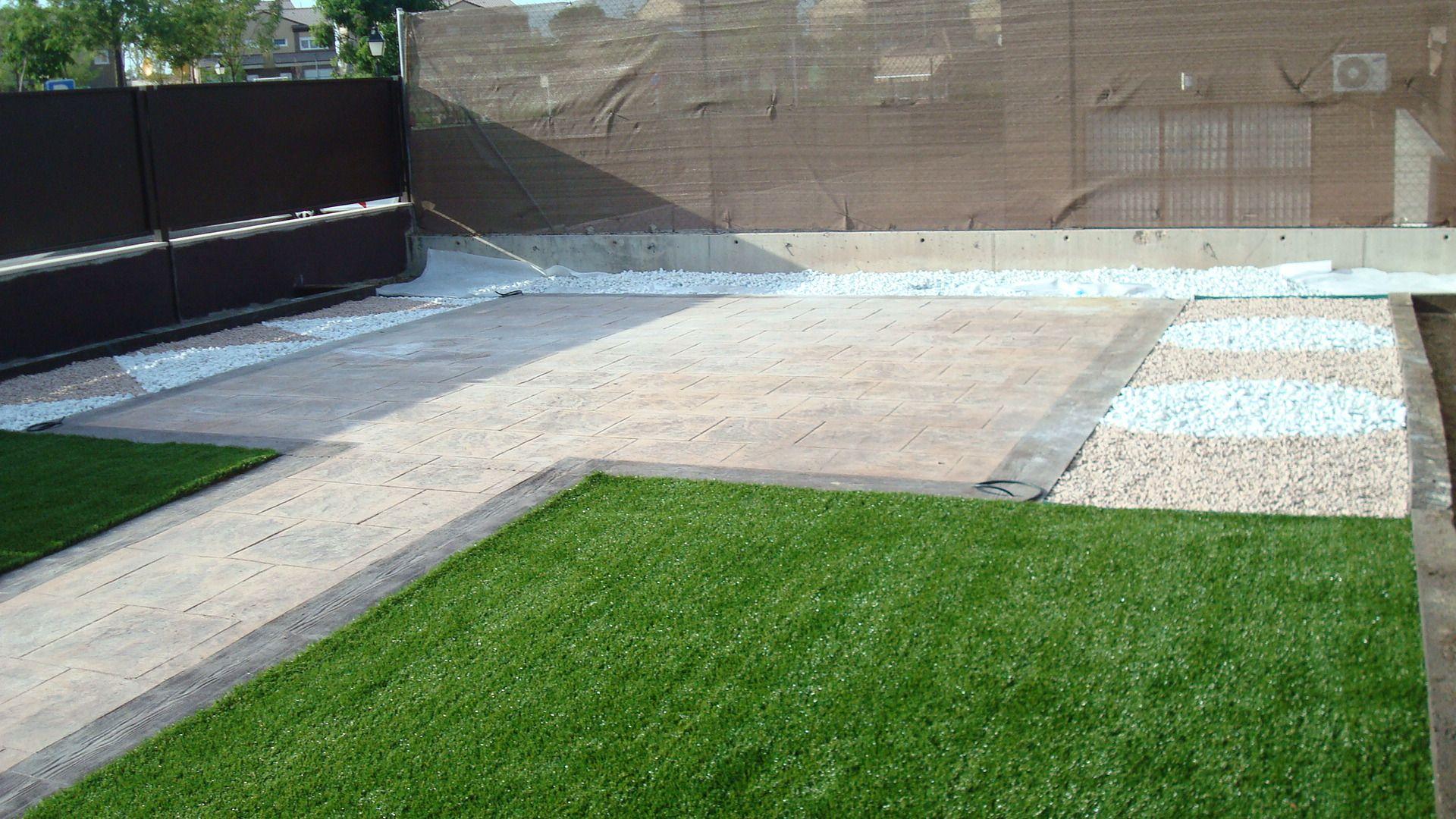 jardin con cesped artificial y decoracion con canto rodado blanco y ...