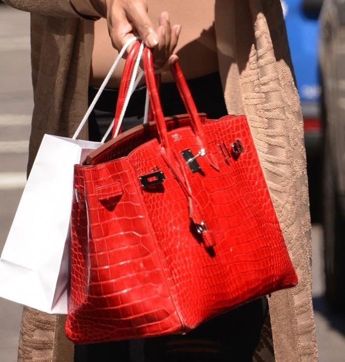 47669208532 EJ Johnson carrying a fiery red Hermes Crocodile Birkin, which has a price  tag of