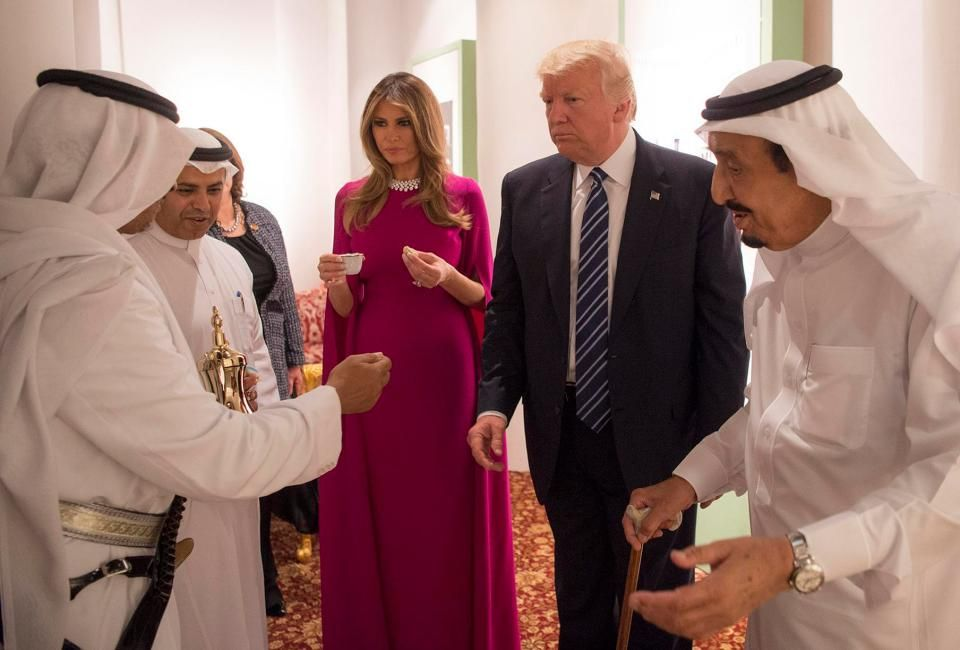 Melania Trump wears a purple cape-style floor-length dress with matching  patent leather pumps at Murabba Palace in Saudi Arabia, escorted by King  Salman for ...