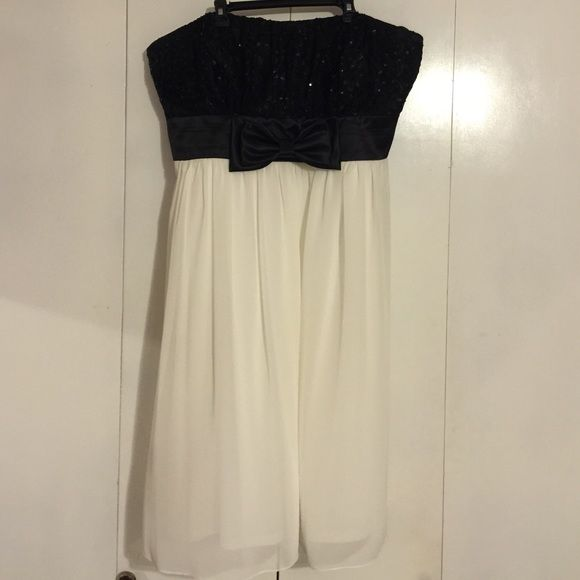 Strapless Formal Black and Cream Dress This cute knee-length tuxedo-inspired formal includes a shawl! The sequins and lace detail is accented nicely with a satin bow! Side hidden zipper. Only used once! Size is 20W! Marina Dresses