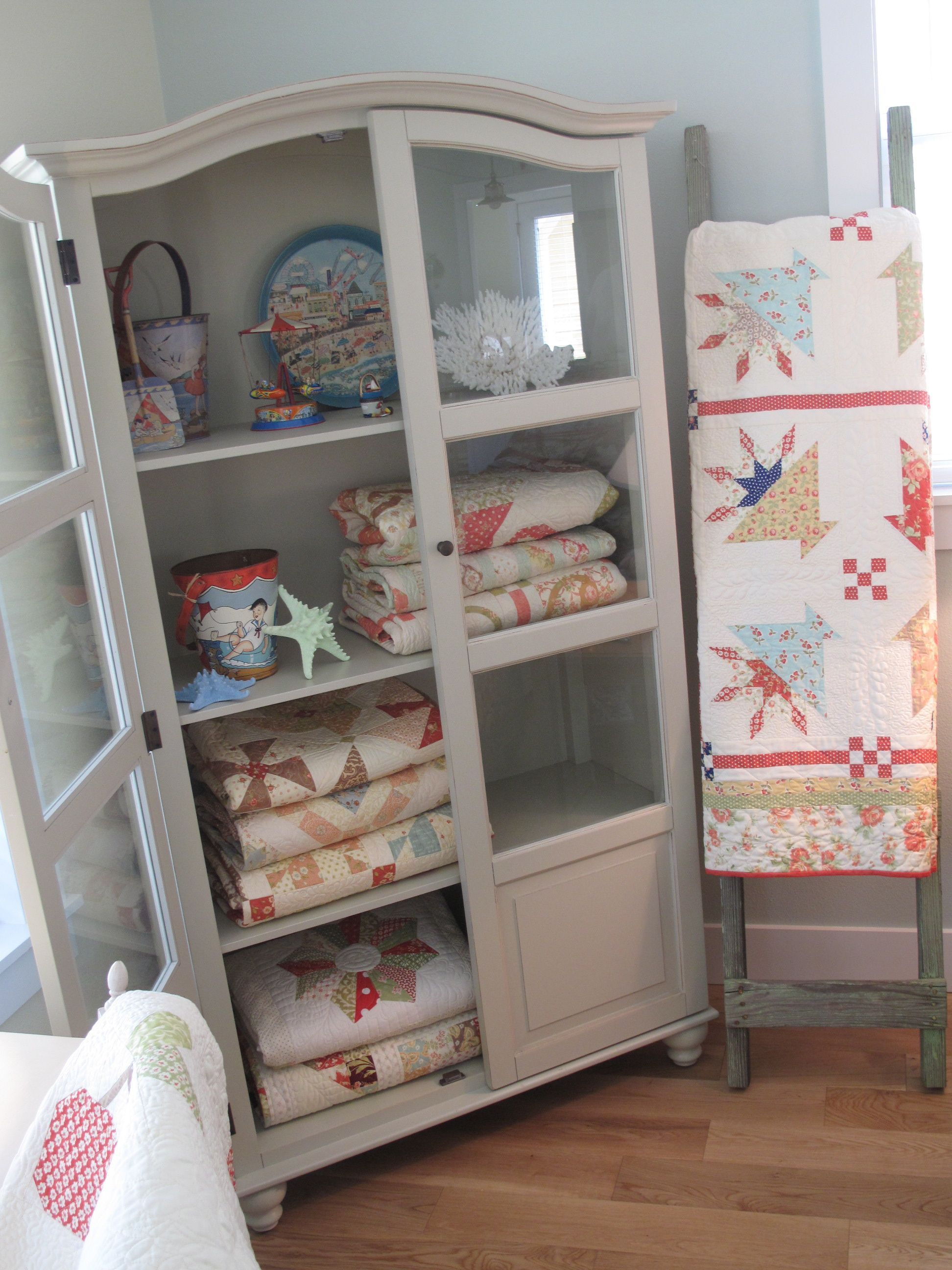 Quilts neatly folded and stacked in a cupboard Isn t it a beautiful