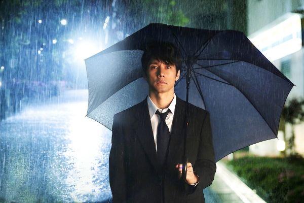 大雨の中に立つ西島秀俊さん