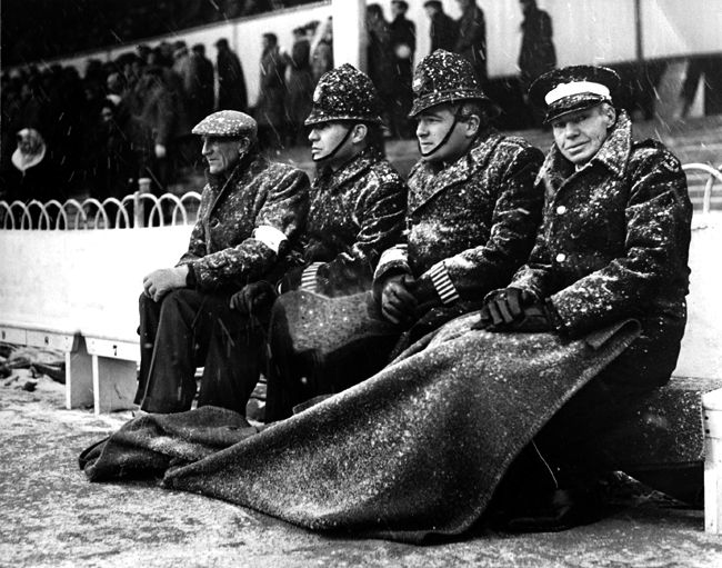 1963:Policemen and ambulance-men attend football a game during a blizzard in London. (Fox Photos/Getty Images)