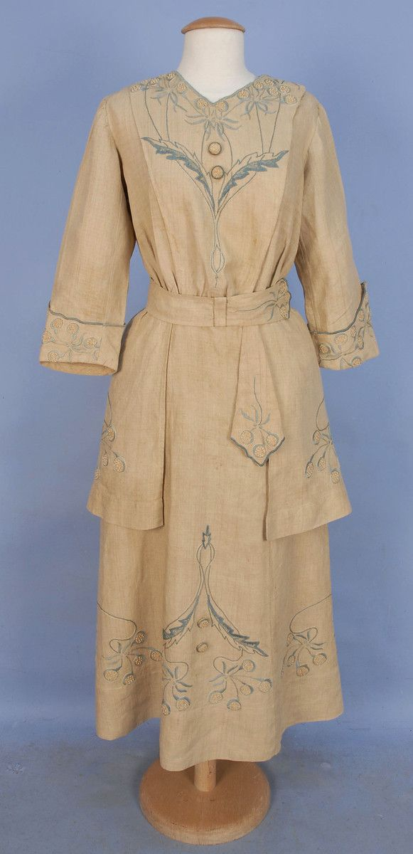 ARTS & CRAFTS EMBROIDERED DAY DRESS, EARLY 20th C. 1-piece natural linen decorated with blue and cream floral satin stitch and French knots, V-neck, 3/4 cuffed sleeve, self belt and side hip panels, faux self buttons with embroidery