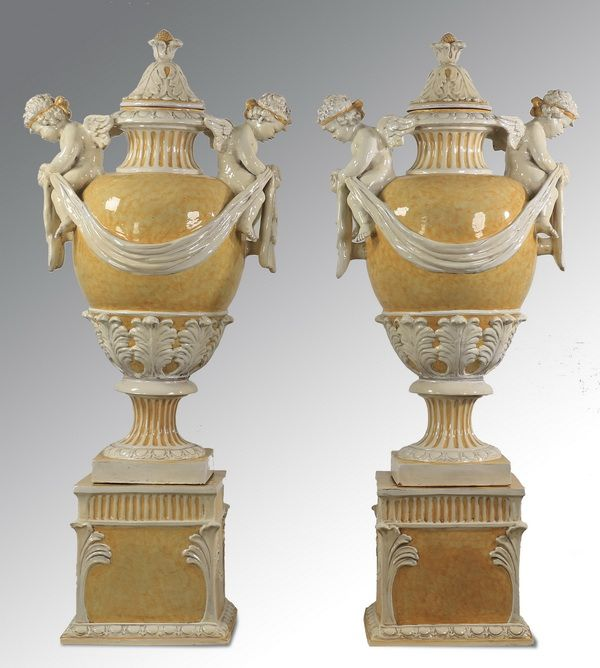Pair of monumental Italian majolica urns, 20th century, each surmounted by an acanthus decorated lid with finial, with two figural seated putti on either side holding drapery swags, the body of the urn with molded acanthus leaf decoration, the whole resting on a square base.