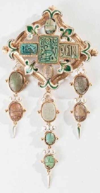 An Egyptian Revival brooch, 19th century. Containing amulets dating from the New to the Late Kingdoms (1550-332 BC), and further decorated with lily motifs, mounted in gold. #EgyptianRevival #brooch