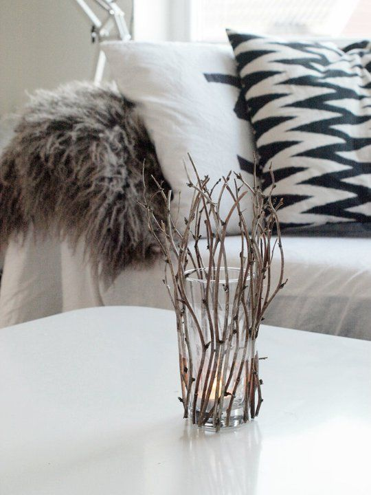Scandinavian Christmas Design Natural twigs around a glass candle holder cast a lovely divided light in the evening.