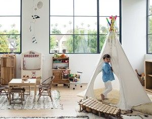 The playroom is stocked with natural wooden toys by Camden Rose and a tipi customized ...