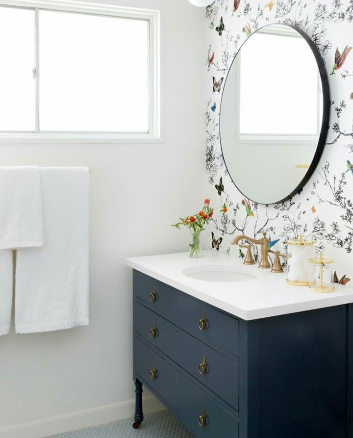 Blue furniture vanity with white counter, brass fixtures