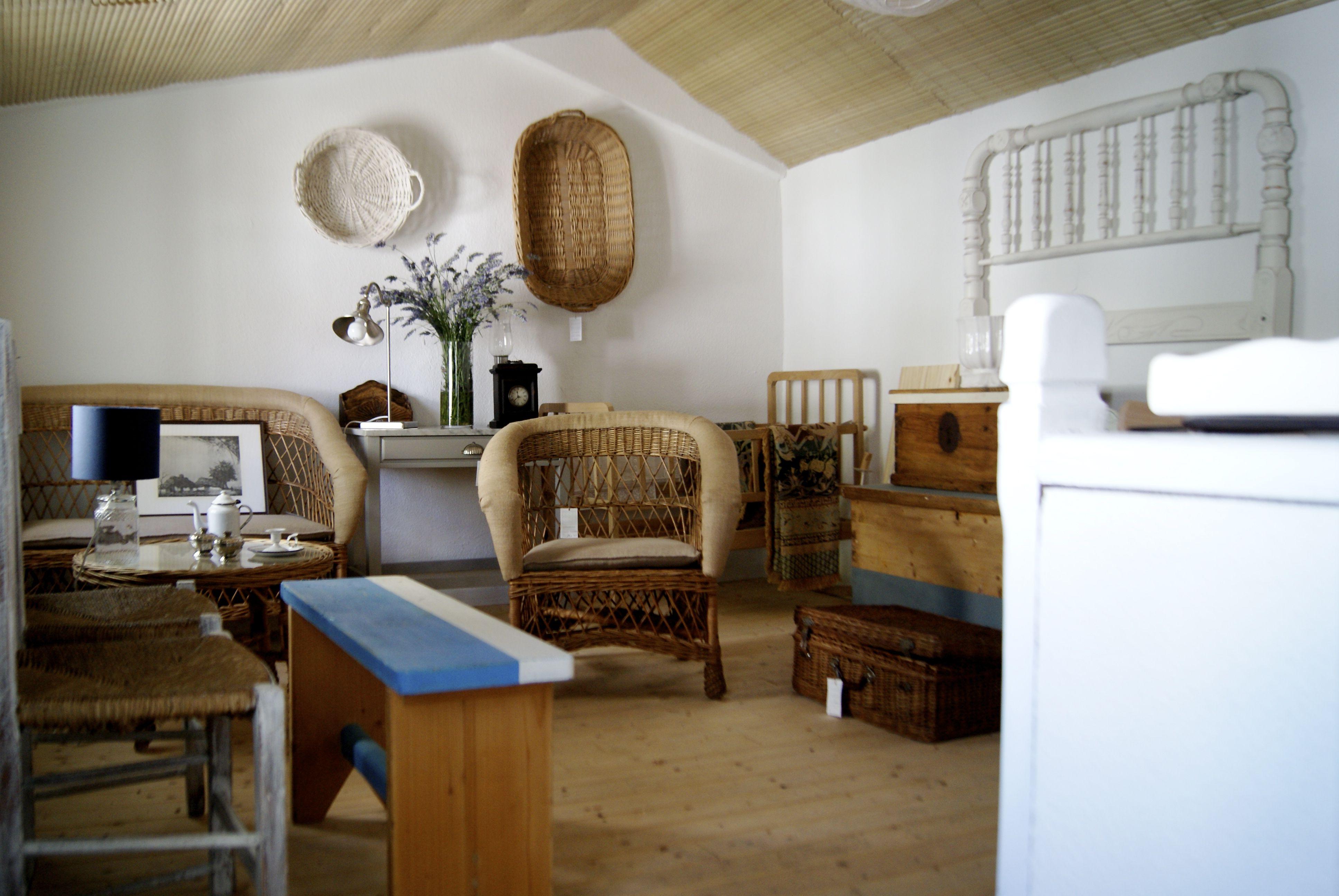 Muebles de mimbre y madera tratada en tonos tierra y azules.