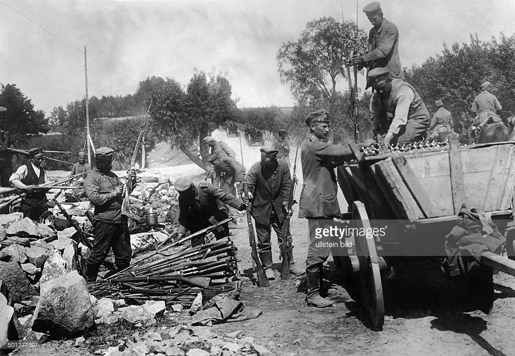 German soldiers load spoils of war (rifles) on to a cart. Near Bubje, Lithuania - summer 1915