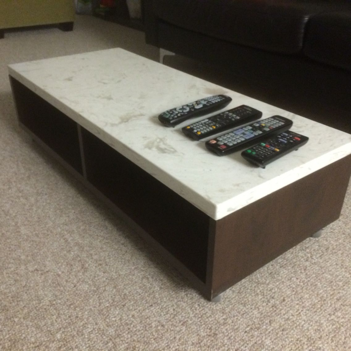 Custom built apartment size Granite coffee table with wood finished and wheels for rolling around for easy cleaning.