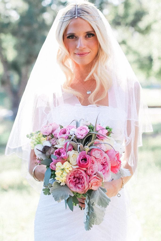 The bride carried a bouquet of ranunculus, garden roses, air plant, stock, cotton, and dusty miller. Photo by Elate Photo