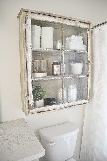 トイレの上の収納棚 ヴィンテージ感あふれる木の質感とガラス扉の組み合わせが暗くなりがちなトイレ周りを明るくしてくれます。普通の置くタイプの棚は足回りを掃除するのが面倒ですがこれなら大丈夫!見せる収納で必要なものがどこにあるかすぐにわかるのもいいですね。