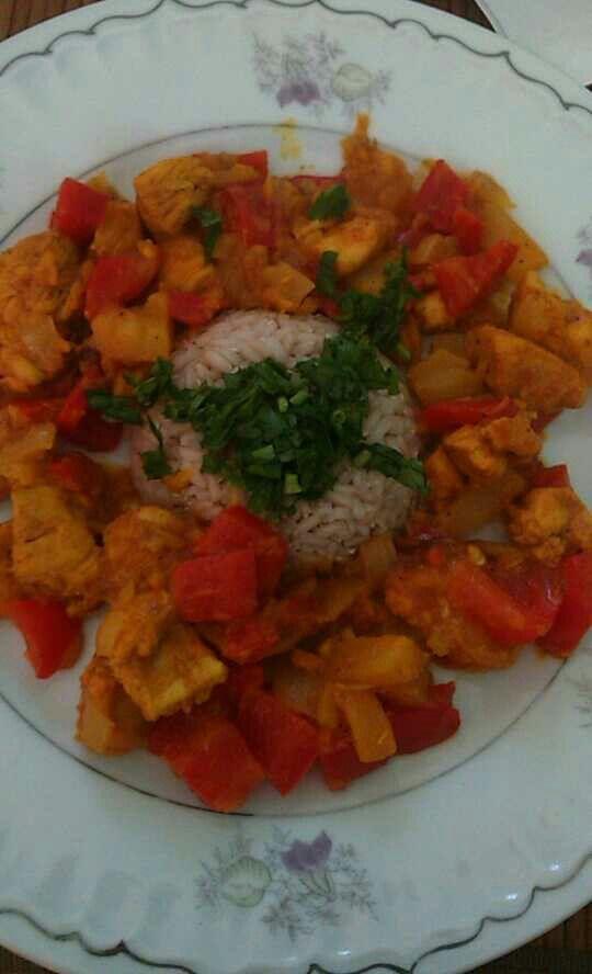 Kurczak w curry i kurkumie w soku pomarańczowym, z papryką, cebulą, pomarańczą i ryżem, posypany koperkiem.