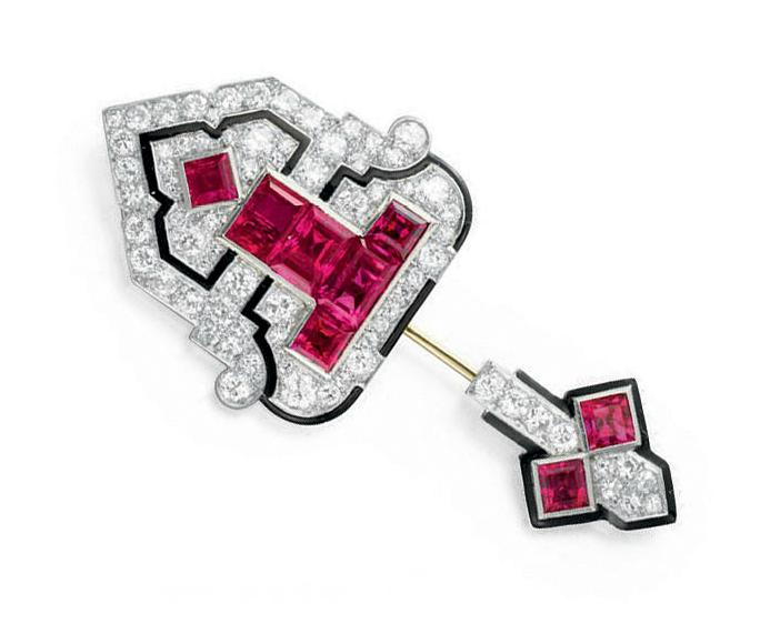 AN ART DECO RUBY, DIAMOND AND ENAMEL JABOT PIN, BY CARTIER Designed as a circular-cut diamond shield-shaped plaque with a central baguette and square-cut ruby geometric pattern and black enamel detail, to the white gold pin and smaller terminal of similar design, mounted in platinum, circa 1925 Signed Cartier, no. 2533